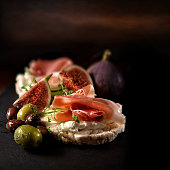 Creatively lit fresh Italian canapes with cream cheese, Serrano cured ham, marinated olives and black figs on organic rice crackers shot against a rustic background with accommodation for copy space.