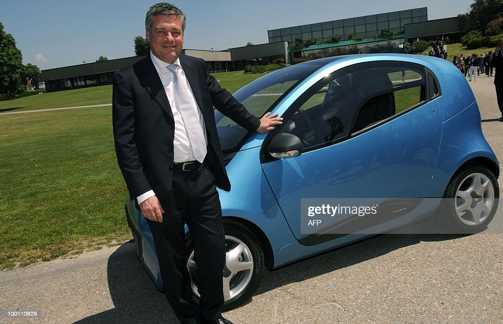 Italian car maker Pininfarina President Paolo Pininfarina poses next to the new Pininfarina electric car 'Nido' during the 80th anniversary celebrations of the Pininfarina group in Cambiano near Turin on May 21, 2010.