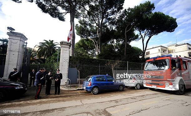 Italian Carabinieri and firemen stand in front of the Swiss embassy in Rome on December 23 2010 A parcel bomb exploded in the Swiss embassy in Rome...