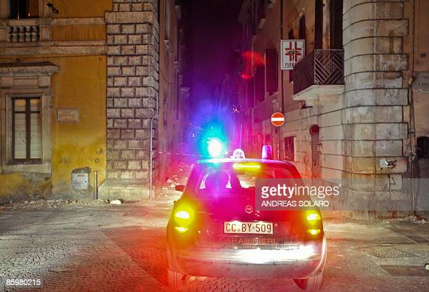 Italian Carabinieri car drive in the streets during on a night patrol of the collapsed buildings of the devastated city of L'Aquila on April 14...