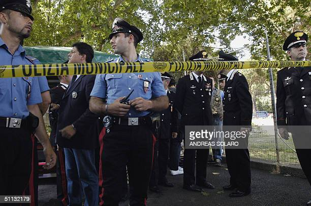 Italian Carabinieri stand next a drinks stall in Rome's Circo Massimo central street near the FAO headquarters after police wounded and captured...