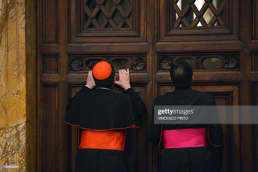 Italian cardinal Giuseppe Betori (L) and a bishop take a glimpse through a door during the courtesy visit to the cardinals on November 24, 2012 at the Apostolico palace at the Vatican. Six non-European prelates are set to join the Catholic Church's College of Cardinals, a move welcomed by critics concerned that the body which will elect the future pope is too Eurocentric.