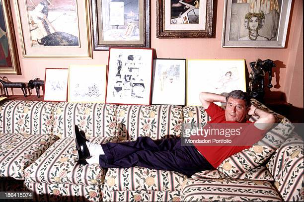 Italian cartoonist and publisher Sergio Bonelli also known as Guido Nolitta keeping his arms behind his head lying on a sofa Behind him some drawings...