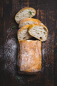Italian ciabatta bread cut in slices on dark wooden background