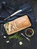 Italian ciabatta bread cut in slices on wooden chopping board with herbs, garlic and olives over dark grunge backdrop, top view