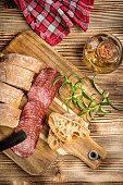 Italian ciabatta bread cut in slices on wooden chopping board with salami.
