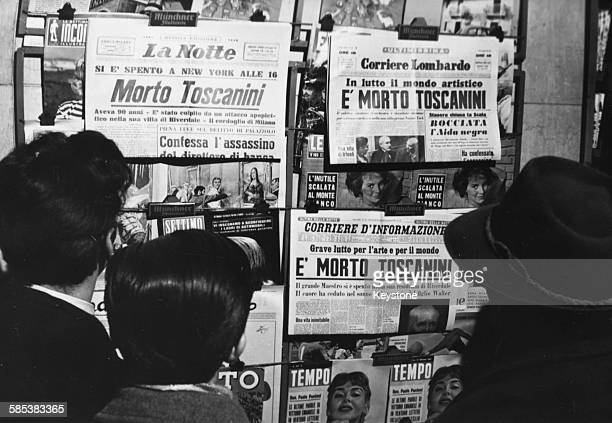 Italian citizens reading copied of the evening newspapers as headlines announce the death of famous conductor Arturo Toscanini Milan January 16th 1957
