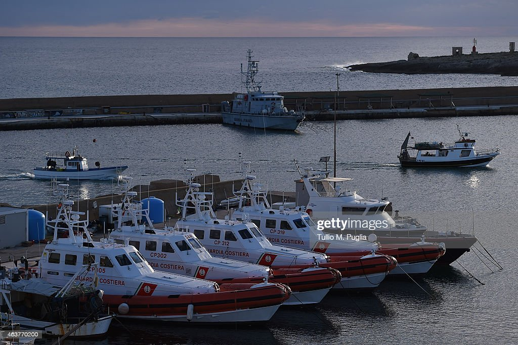 Italian Coast Guard patroll boats are moored in the port of Lampedusa near Favaloro Pier pictured in the background where migrants arrive after being...