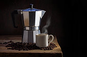 Italian coffee maker, cup of steaming coffee and whole coffee beans on an old rustic wooden table against a dark brown background with generous copy space