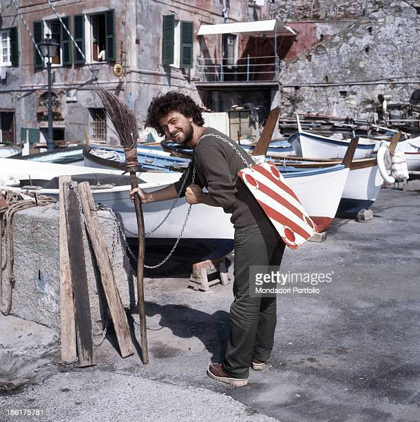 Italian comedian actor and politician Beppe Grillo holding a sorghum broom in his right hand and keeping a protruding loads sign on his back Genoa...