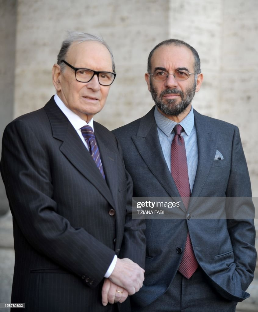 Italian composer and conductor Ennio Morricone (L) poses with Italian director Giuseppe Tornare as they arrive for a projection of 'The Best Offer', a film by Tornatore, on December 28, 2012, in Rome.