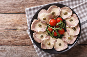 Italian cuisine: Vitello tonnato with capers, arugula, tomatoes on a plate close-up. horizontal view from above