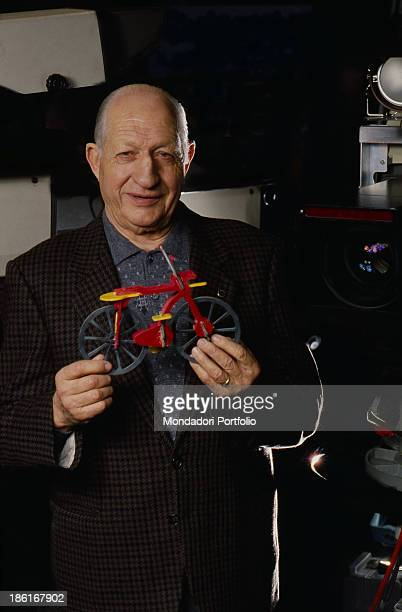 Italian cyclist and sports manager Gino Bartali smiling holding a bike toy model 1990s