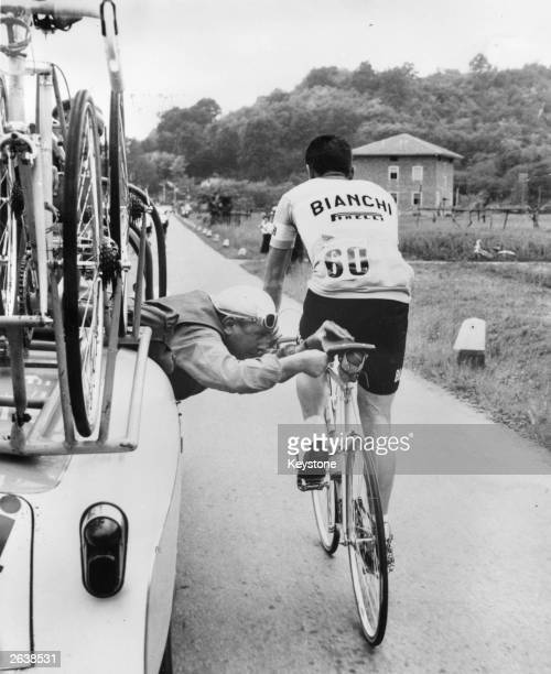 Italian cyclist Brandolini of the Bianchi team gets a 'flying saddle' repair from one of his mechanics in a car during a Tour of Italy cycle race