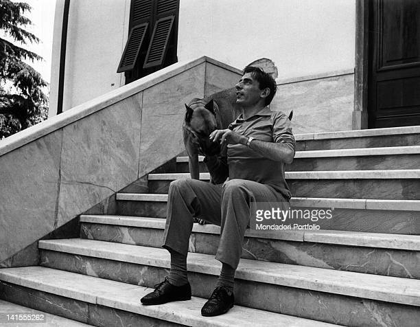 Italian cyclist Fausto Coppi petting a dog while sitting on some steps 1950s