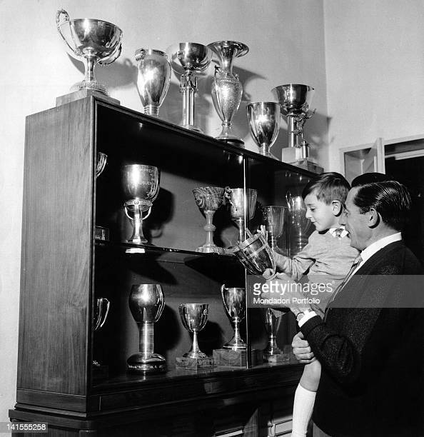 Italian cyclist Fausto Coppi showing his son Angelo Fausto some trophies that he won 1959