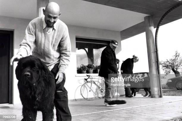 Italian cyclist Marco Pantani Tour de France and Giro d'Italia race winner in 1998 plays with his dog with his father Paolo and his girlfriend...