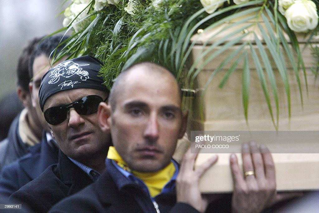 Italian cyclist Vladimir Belli (foreground) and other friends carry the coffin containing the body of Italian cycling champion Marco Pantani in the streets of his home town in Cesenatico, 18 February 2004. The funerals have been followed by a huge crowd. Pantani died, 14 February 2004 in a residence-hotel in the resort city of Rimini. AFP PHOTO Paolo COCCO