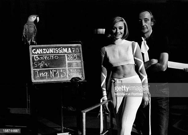 Italian dancer and presenter Raffaella Carrà in an evening dress showing her navel in the studio of Canzonissima with broadcast director Romolo Siena...