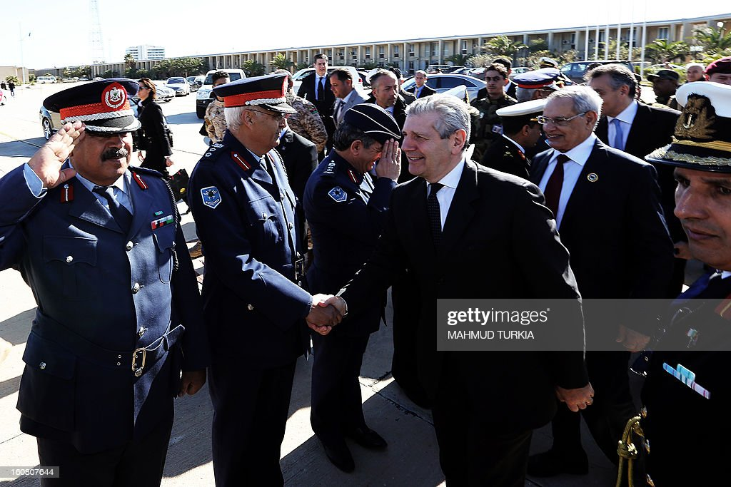 Italian Defence Minister Giampaolo di Paola (C) and Libya's Defense Minister Mohammed al-Barghathi (2nd R) are greeted by Libyan officers on February 6, 2013 at a Libyan Navy Base during a ceremony for the hand over 20 military vehicles to Libya in Tripoli.