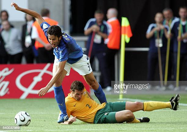 Italian defender Fabio Grosso falls after fighting for the ball with Australian defender Lucas Neill during the round 16 World Cup football match...