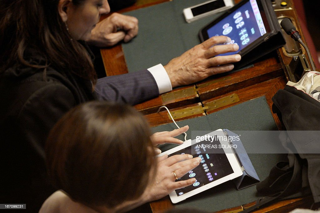Italian deputies count votes on their tablets in the Italian Parliament on April 20, 2013 during the election of Italy's President. Italy's 87-year-old President Giorgio Napolitano said on Saturday said he would run for a second term despite earlier ruling out the prospect, following an appeal from the main parties to help defuse an increasingly tense political crisis. 'I consider it necessary to offer my availability,' Napolitano said in a statement, as bickering lawmakers prepared for a sixth round of voting in parliament that he is now expected to win by a large margin.