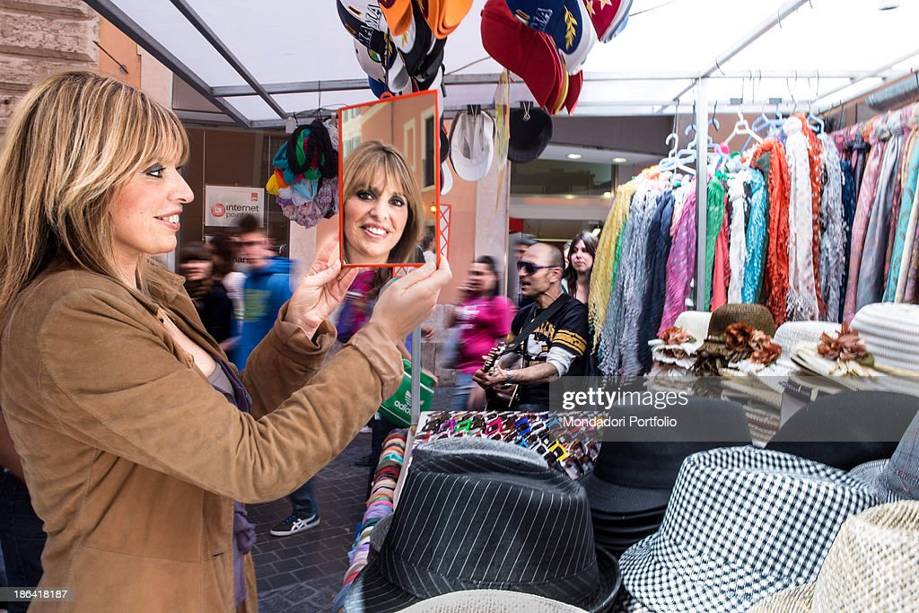 Italian deputy <a gi-track='captionPersonalityLinkClicked' href=/galleries/search?phrase=Alessandra+Mussolini&family=editorial&specificpeople=243183 ng-click='$event.stopPropagation()'>Alessandra Mussolini</a> looking at herself in the mirror in front of a market stall. Rome, 27th April 2012.