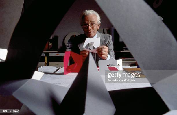 Italian designer and artist Bruno Munari showing the paper scale model of a chair 1986