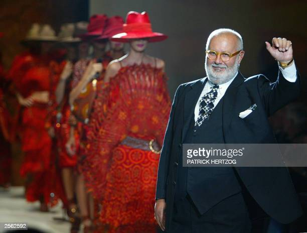Italian designer Gianfranco Ferre waves to the audience after the presentation of his collection 03 October 2003 during the Spring/Summer 2004...