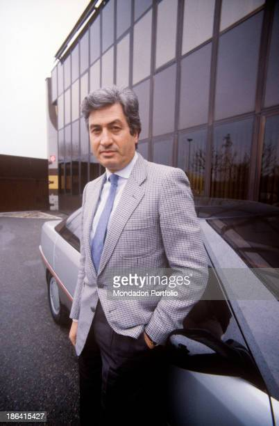 Italian designer Giorgetto Giugiaro leaning against a car with a hand in pocket 1980s