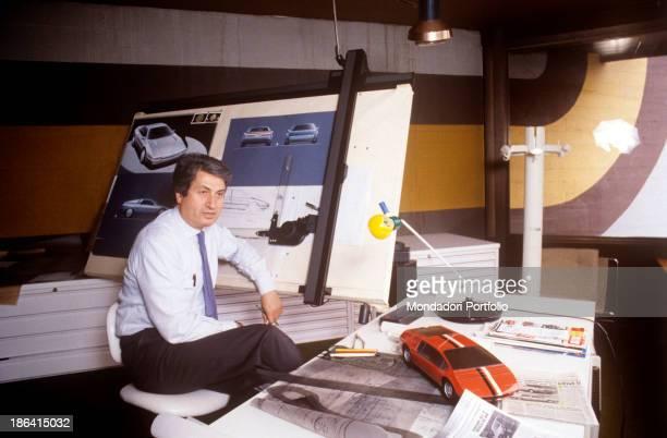 Italian designer Giorgetto Giugiaro sitting in his office in front of a drawing board 1987