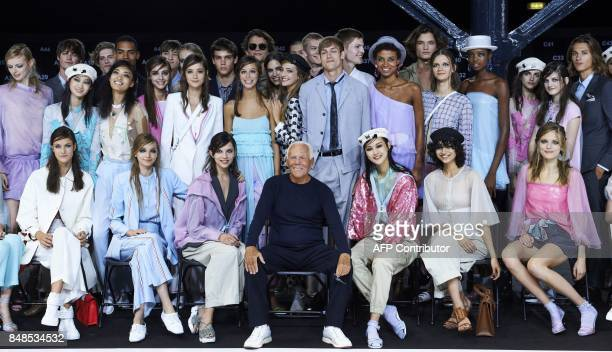 Italian designer Giorgio Armani poses for a photograph next to models after the fashion house Emporio Armani catwalk show for the Spring/Summer 2018...