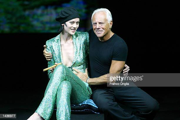 Italian designer Giorgio Armani sits next to a model at the end of Emporio Armani Spring/Summer women's collection for 2003 September 28 2002 in...