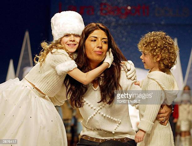 Italian designer Laura Biagotti embraces the young girls who presented her 2004/2005 fallwinter creations 17 January 2004 in Florence during the...