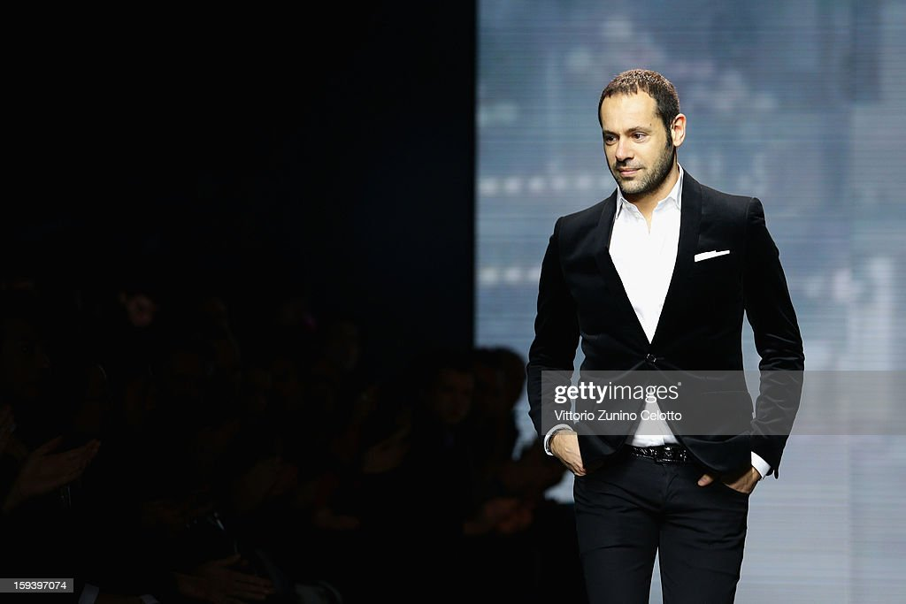 Italian designer <a gi-track='captionPersonalityLinkClicked' href=/galleries/search?phrase=Massimiliano+Giornetti&family=editorial&specificpeople=3951751 ng-click='$event.stopPropagation()'>Massimiliano Giornetti</a> acknowledges the audience at the end of the Salvatore Ferragamo show as part of Milan Fashion Week Menswear Autumn/Winter 2013 on January 13, 2013 in Milan, Italy.