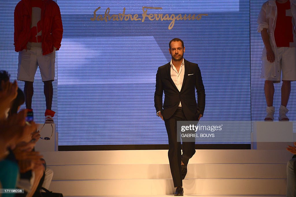 Italian designer Massimiliano Giornetti acknowledges the audience at the end of the Salvatore Ferragamo Spring-Summer 2014 Menswear collection on June 23, 2013 during the fashion week in Milan. AFP PHOTO / GABRIEL BOUYS