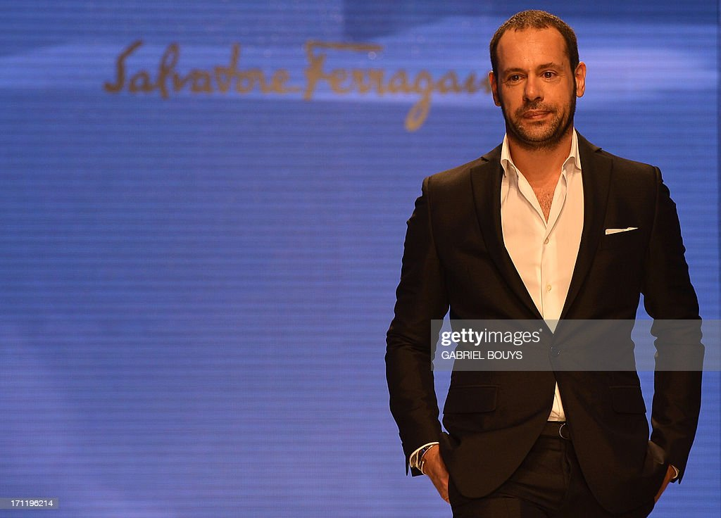 Italian designer Massimiliano Giornetti acknowledges the audience at the end of the Salvatore Ferragamo Spring-Summer 2014 Menswear collection on June 23, 2013 during the fashion week in Milan.