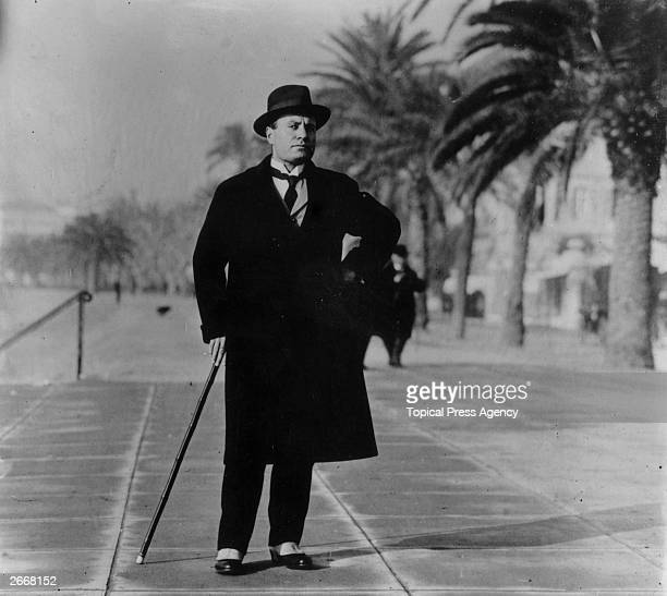 Italian dictator Benito Mussolini wearing spats and an overcoat on the Boulevard at Biarritz France