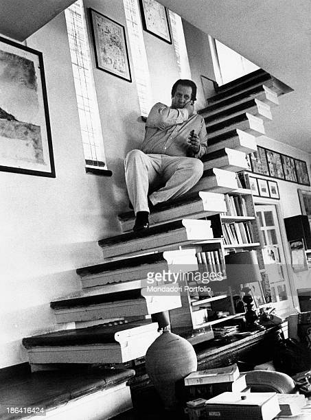 Italian director and playwright Tinto Brass sitting on the steps of the staircase leading to the bedrooms in his country house Rome 1979