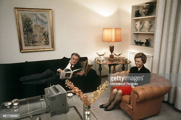 Italian director and scenarist Federico Fellini reading a book lying on a sofa while his wife and Italian actress Giulietta Masina is watching the TV...