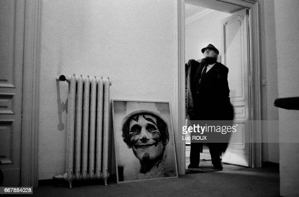 Italian director and screenwriter Federico Fellini in the doorway of his office in Rome Propped against the wall is a portrait of famous clown Grock...