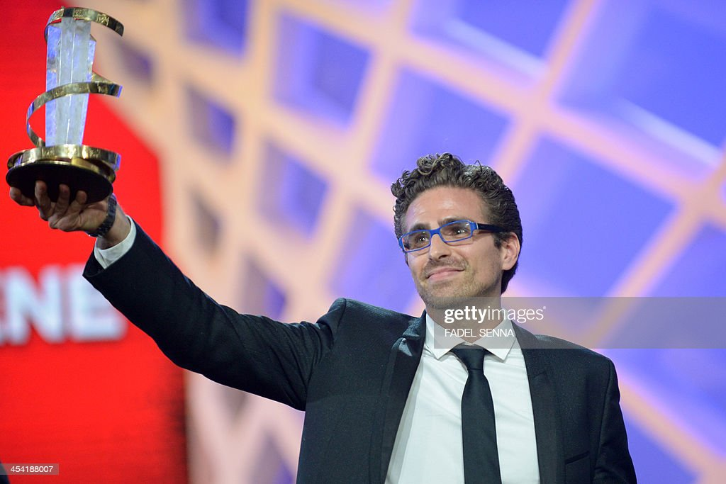 Italian director Andre Pallaoro holds his 'best director prize' during the closing ceremony of the 13th Marrakech International Film Festival on December 7, 2013 in Marrakech.