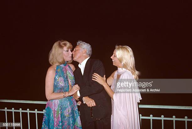 Italian director Dino Risi kissing Italian actress Sylva Koscina ij front of Italian actress Mariangela Melato at the David di Donatello awarding...