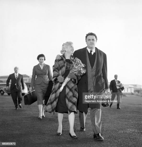 Italian director Federico Fellini accompanying Italian actress Giulietta Masina to the plane that will bring Giulietta to Berlin for a movie Ciampino...