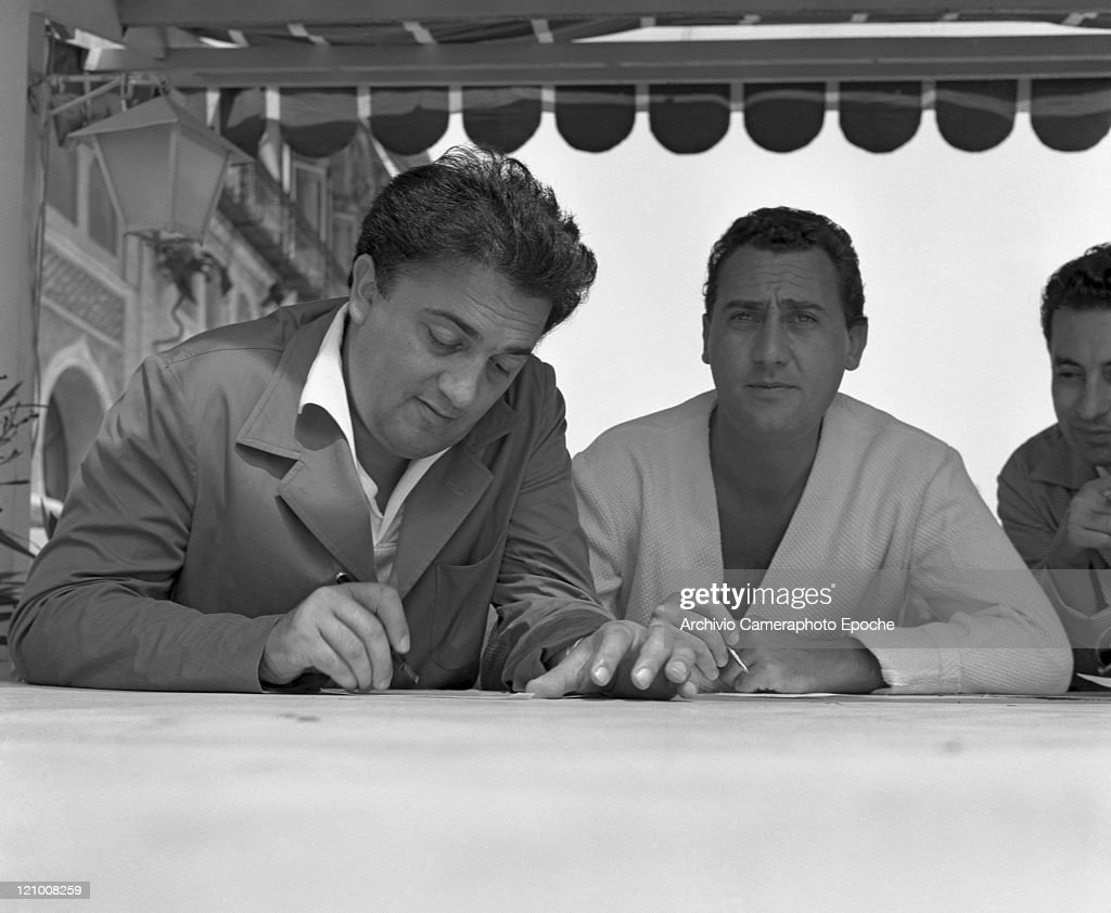 Italian director <a gi-track='captionPersonalityLinkClicked' href=/galleries/search?phrase=Federico+Fellini&family=editorial&specificpeople=243035 ng-click='$event.stopPropagation()'>Federico Fellini</a> portrayed while signing autographs with the italian actor Alberto Sordi, in Lido, Venice for presenting the movie 'I Vitelloni' at the Movie Festival, 1953.
