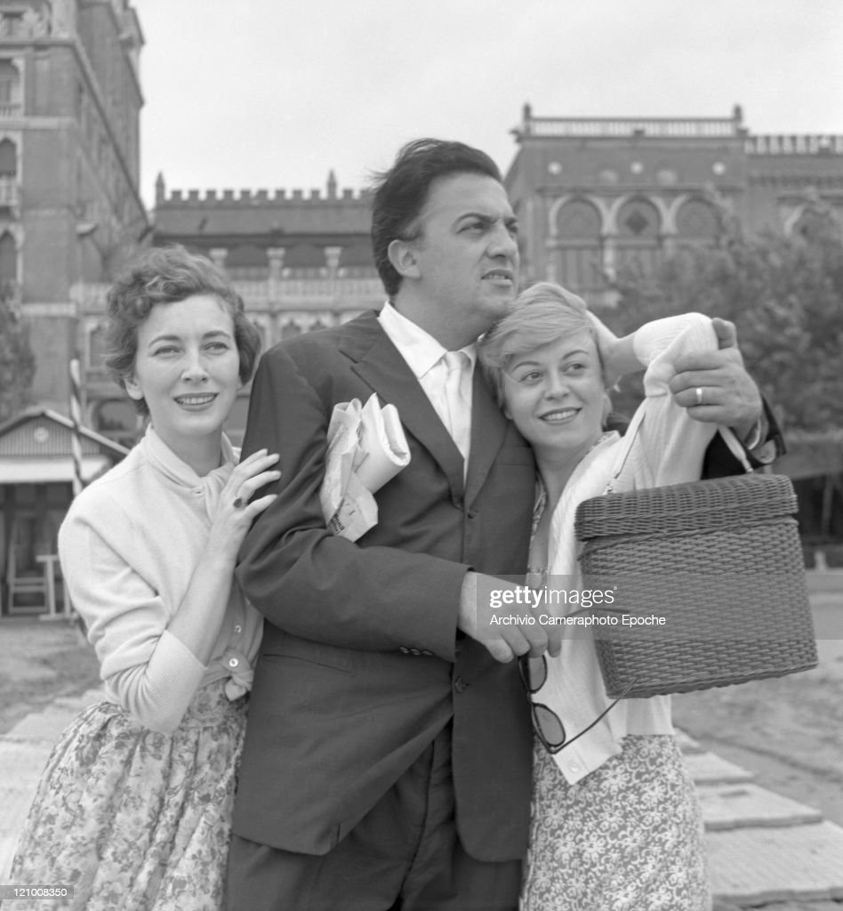 Italian director <a gi-track='captionPersonalityLinkClicked' href=/galleries/search?phrase=Federico+Fellini&family=editorial&specificpeople=243035 ng-click='$event.stopPropagation()'>Federico Fellini</a>, wearing a suit and holding sunglasses, portrayed among the actress Valentina Cortese and his wife Giulietta Masina in front of the Excelsior hotel, Lido, Venice 1955.