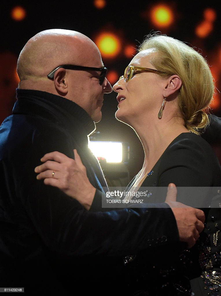 Italian director Gianfranco Rosi embraces US actress and jury president Meryl Streep after receiving the Golden Bear for Best Film for the film...