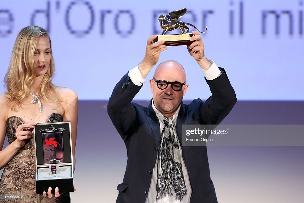 Italian director Gianfranco Rosi (L), flanked by Eva Riccobono, poses with the Golden Lion for Best Film. He received the award for his movie 'Sacro Gra' during the award ceremony of the 70th Venice Film Festival at the Palazzo del Cinema on September 7, 2013 in Venice, Italy.