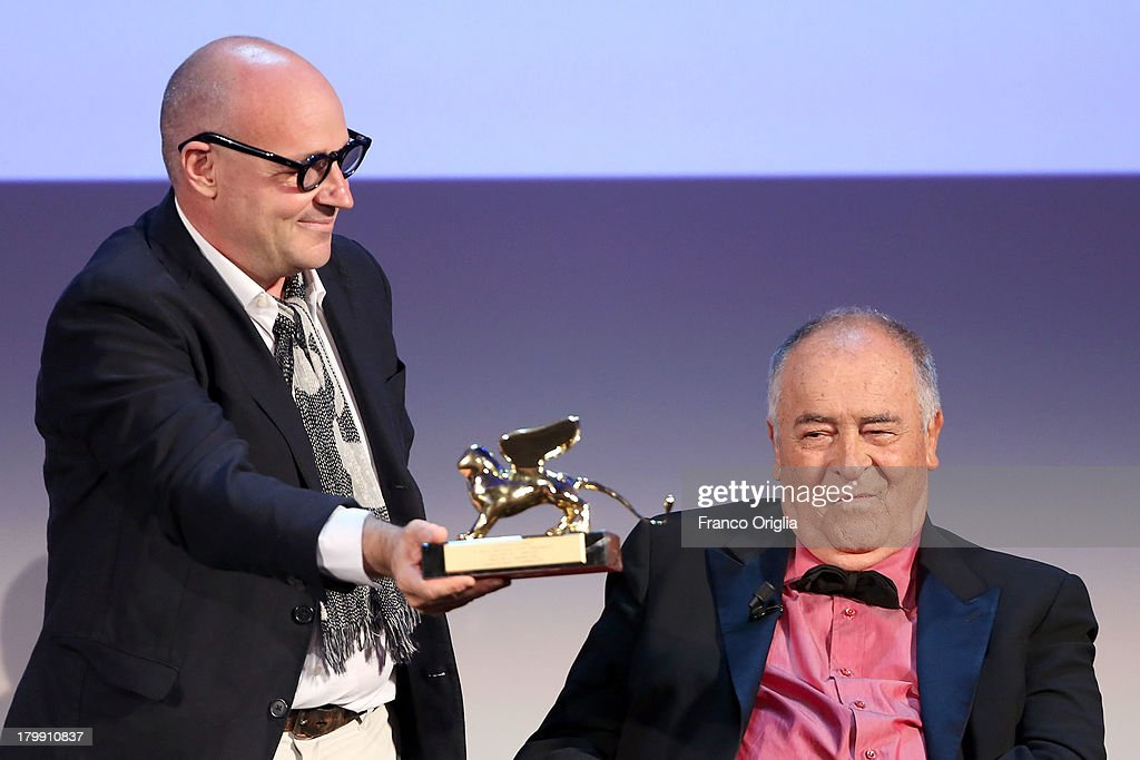 Italian director Gianfranco Rosi (L), flanked by International Jury President <a gi-track='captionPersonalityLinkClicked' href=/galleries/search?phrase=Bernardo+Bertolucci&family=editorial&specificpeople=228513 ng-click='$event.stopPropagation()'>Bernardo Bertolucci</a>, poses with the Golden Lion for Best Film he received for his movie 'Sacro Gra' during the award ceremony of the 70th Venice Film Festival at the Palazzo del Cinema on September 7, 2013 in Venice, Italy.