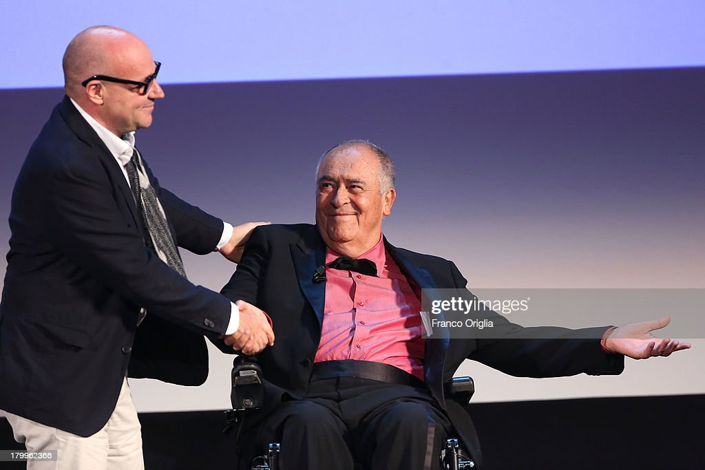 Italian director Gianfranco Rosi (L), flanked by International Jury President Bernardo Bertolucci, poses with the Golden Lion for Best Film he received for his movie 'Sacro Gra' during the award ceremony of the 70th Venice Film Festival at the Palazzo del Cinema on September 7, 2013 in Venice, Italy.